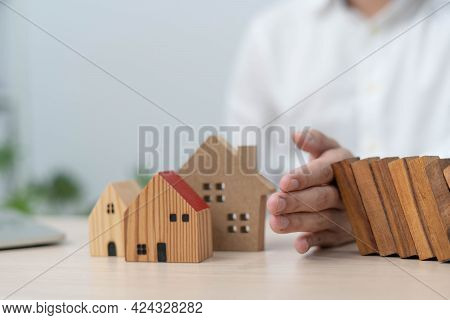 Insurance With Hands Protect A House. The Wooden Domino Block Is About To Fall On The House. Home In