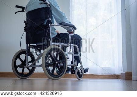 A Leg-disabled Man Sits On A Wheelchair. The Disabled Sat In The Room Lonely And Frustrated.