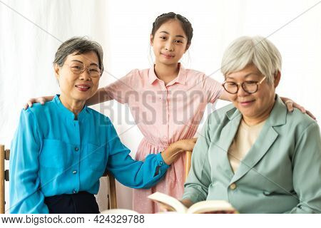 Portrait Of Happy Asian Grandmother And Little Asian Cute Girl Enjoy Relax In Home.young Girl With T