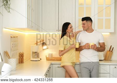 Happy Couple Wearing Pyjamas With Cups Of Coffee In Kitchen