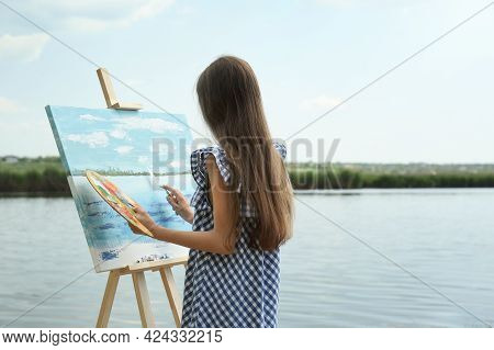 Little Girl Painting Scenery On Easel Near Lake, Back View