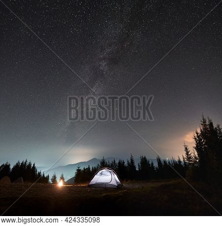 Bright Tent Near Forest And Campfire. Cozy Place For Camping In Mountains Under Shining Sky Covered