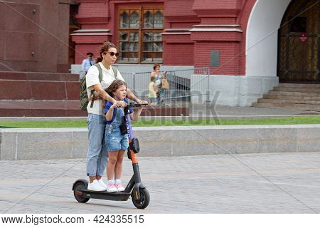 Moscow, Russia - June 2021: Woman With Little Girl Rides An Electric Scooter On A Street. Mother Wit