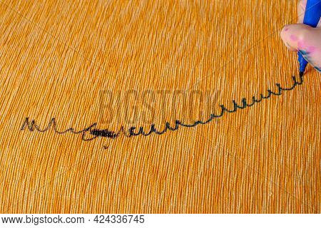 Children's Hand Draws A Felt-tip Pen On The Upholstery Of The Yellow Sofa. Top View