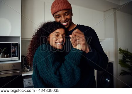 Young, Happy Mixed Race Couple Holding Hands In The Kitchen. Mixed Race Couple Dancing Together And