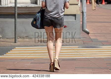 Slim Girl In Short Jeans Shorts And High Platform Shoes Goes To The Crosswalk. Female Fashion In Hot