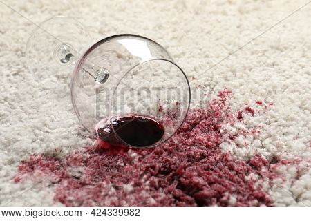 Overturned Glass And Spilled Red Wine On White Carpet, Closeup