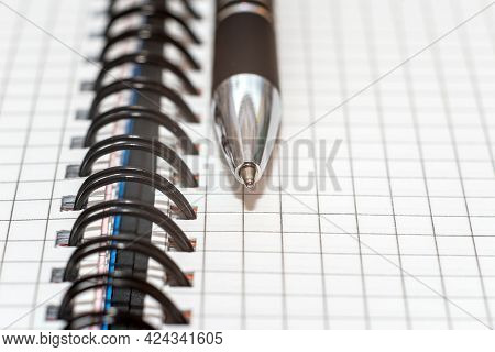 Ballpoint Pen On The Background Of A Sheet Of Checkered Paper.close Up,macro Shot.