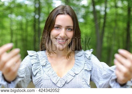 Front View Portrait Of A Happy Woman Saying Come Here Beckoning With Both Hands In A Park
