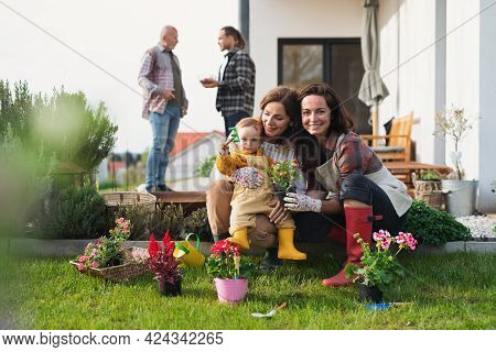 Happy Multigeneration Family Outdoors Planting Flowers In Garden At Home, Gardening Concept.