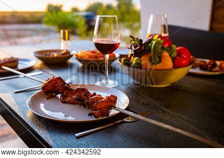 Laid table with food on the summer terrace. Food on the terrace at sunset. Sunset with a laid table
