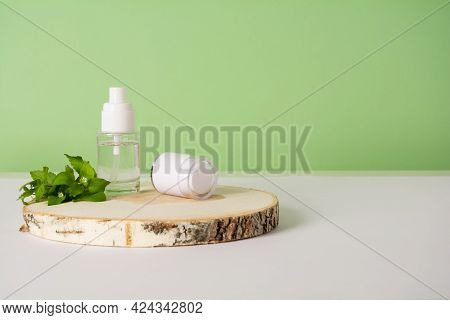 Cosmetics Bottle With Beauty Product And Wild Plants On Green Background. Liquid Skin Or Hair Care P