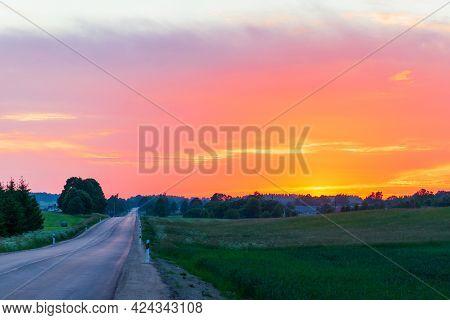 Beautiful Rural Asphalt Road Scenery At Sunset Or Sunrise.asphalt Road Between Fields Trees.beautifu
