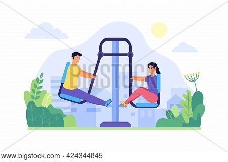 People Swing Feets On Street Trainer. Young Man And Woman Actively Warming Up On Fitness Equipment.