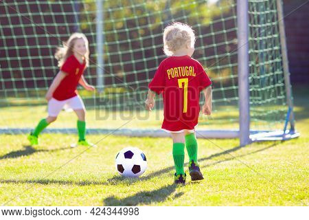 Kids Play Football On Outdoor Field. Portugal Team Fans. Children Score A Goal At Soccer Game. Boy A
