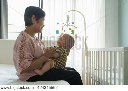 Happy Asian Grandmother Sitting On Bed Holding Her Little Grandchild In Bedroom At Home. Playful Ado