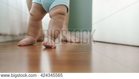 Close Up Asian Mother Holding Her Little Baby Learning To Walk On Wooden Floor At Home. Cute Toddler