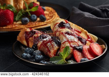 Pancakes with berries  and sweet sauce on black background.  Maslenitsa. Shrovetide. Shrove Tuesday. Pancake Day. Happy holiday, Greeting. Dessert. Serving food
