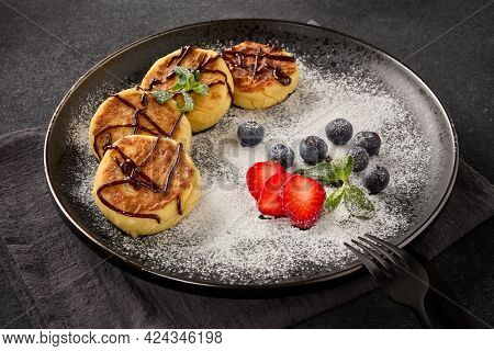 Russian cottage cheese pancakes (Syrniki) with berries, powdered sugar, chocolate sauce on ceramic  plate on black background. Dessert. Serving food