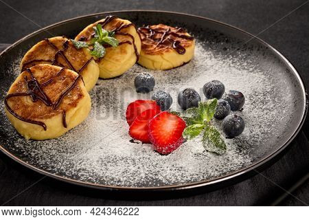 Russian cottage cheese pancakes (Syrniki) with berries, powdered sugar, chocolate sauce on black ceramic  plate. Dessert. Serving food. Food background