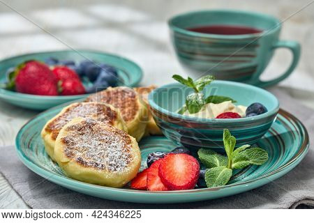 Russian cottage cheese pancakes (Syrniki) with berries and sour cream, cup with fruit tea on light wooden table with sunlight from window. Healthy breakfast. Serving food