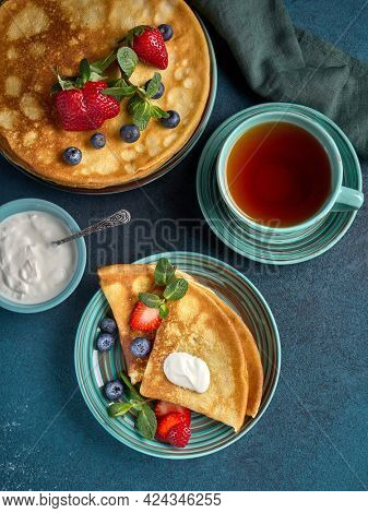Pancakes with berries and sour cream on dark green background. Top view. Maslenitsa. Shrovetide. Shrove Tuesday. Pancake Day. Happy holiday, Greeting. Dessert. Serving food