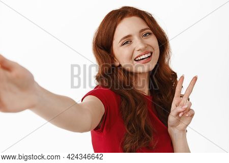 Beautiful And Stylish Redhead Girl Taking Selfie, Video Calling, Showing V-sign At Mobile Phone Came