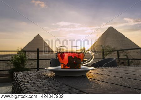 Traditional Arab Tea In A Glass Against The Background Of The Great Pyramids Of Giza. Beautiful View