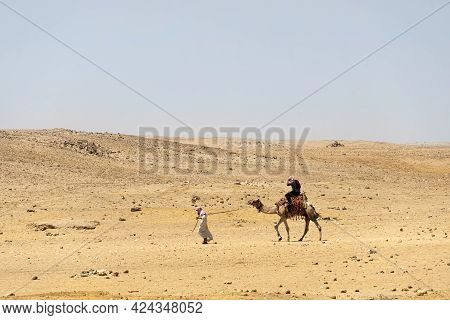 Camel Riders In The Desert, Egypt. A Bedouin Leads A Camel Through The Desert.