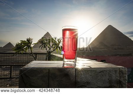 Traditional Arab Herbal Tea Karkade In A Glass Against The Background Of The Great Pyramids Of Giza.