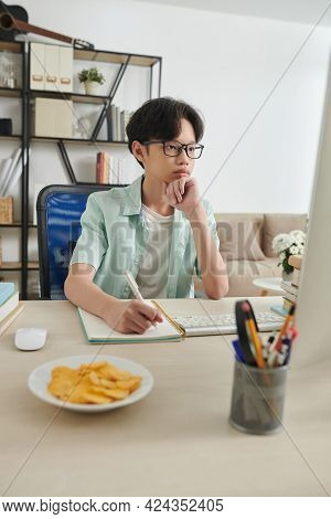 Serious Concentrated Teenage Boy In Glasses Watching Webinar Or Reading Article On Computer And Writ
