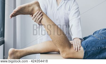 Physical therapy, Male physiotherapist treats legs and hips pain for a male patient attending in cli