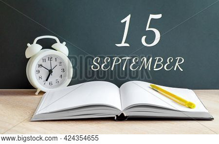 September 15. 15-th Day Of The Month, Calendar Date.a White Alarm Clock, An Open Notebook With Blank