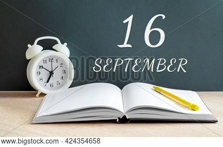 September 16. 16-th Day Of The Month, Calendar Date.a White Alarm Clock, An Open Notebook With Blank