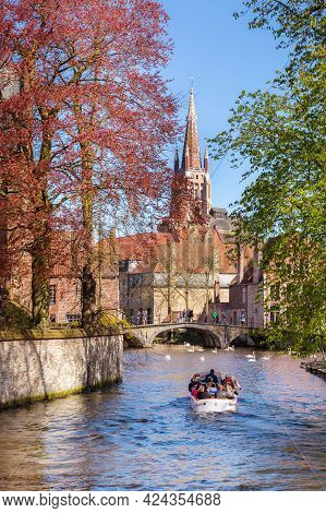Bruges, Belgium - April 10, 2016: Spring View With Canal And Bridge, Boat, Spring Trees And Church T