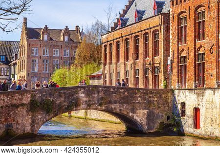 Bruges, Belgium - April 10, 2016: Scenic Cityscape With Houses, People On Bridge And Canal In Bruges