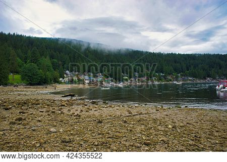 Rock Beach And The Residential Houses Of Deep Cove.  North Vancouver Bc Canada