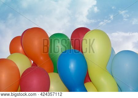 Colorful Oblong Balloons Isolated Against A Blue Sky With Clouds.
