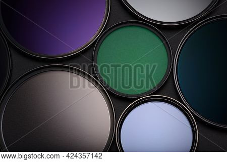 Set Of Various Lens Filters For Slr Camera On Black Background.