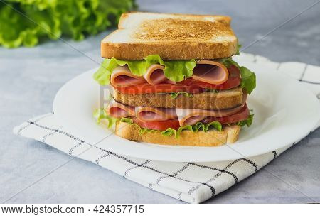 Tasty Sandwich With Ham, Salad, Ham And Tomatoes On Gray Background