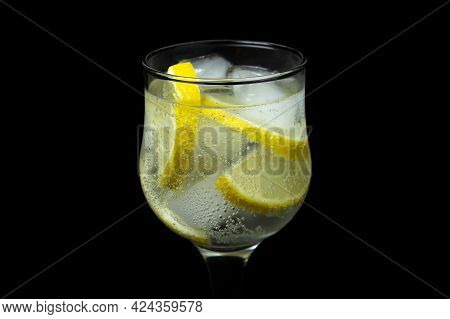 Refreshing Cocktail With Ice And Lemon On A Black Background. Non-alcoholic Cocktail.