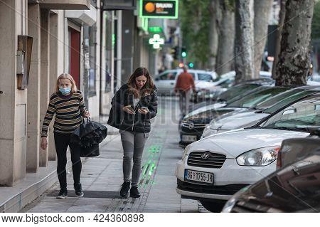 Belgrade, Serbia - May 13, 2021: Old Senior Woman Wearing A Respiratory Facemask  Next To A Young Gi