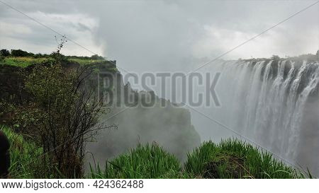 Powerful Streams Of Water Fall Into The Gorge. A Dense Fog Stands Over The Abyss. Tiny Silhouettes O