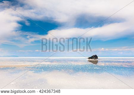 Off-road Car Driving On Salar De Uyuni Salt Flat In Bolivia. Sky With White Clouds Reflected In The