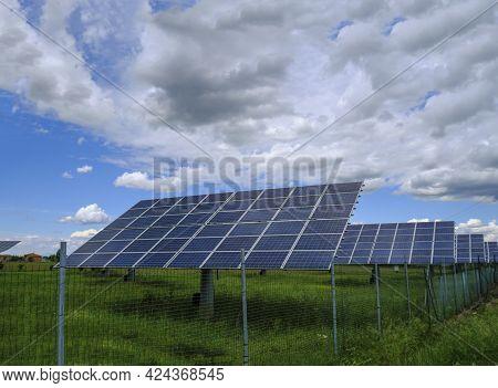 Solar Panels On A Field Across The Dramatic Sky. Solar Energy Industry. Alternative Energy