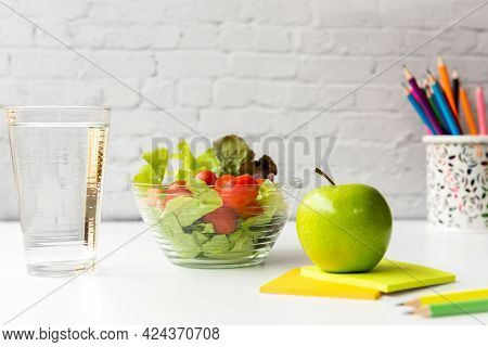 Select Focus. Healthy Snack With Working In Office.  Green Apple And Fresh Salad With Water For Diet