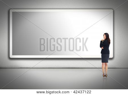 Business woman standing near blank billboard. Advertising concept.