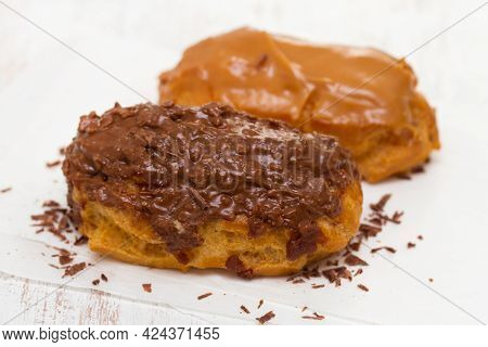 Choclate Eclairs On White Paper On Wooden Background