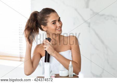 Cheerful Woman Spraying Hairspray Making Ponytail In Bathroom Indoor