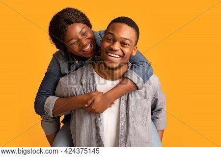Couple Fun. Loving Black Guy Giving Piggyback Ride To His Laughing Girlfriend